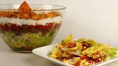 Der Tacosalat besteht aus viel frischem Gemüse, einer Hackfleischschicht, einer selbstgemachten Tacosoße und ist ganiert mit Tortillachips.