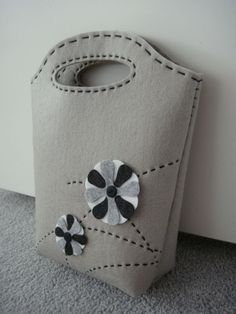 This kit is perfect for novice bag makers like me. It came with pre-cut, pre-punched materials and instructions. It's a simple grey felt bag with monochrome flowers. >Aligning the holes …