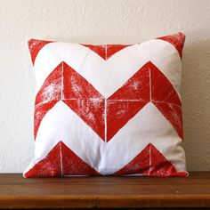 """""""Chevron Pillow Red by Nesta Home"""" Printmaker Tandie Mast of Nesta believes every town, city and piece of land evokes an emotion and she's dedicated to conveying that feeling into her designs. This particular collection takes inspiration from the vast, open spaces of the Sonoran Desert. Using her own hand-carved linocut stamps, she individually hand-prints these comfy cushions."""