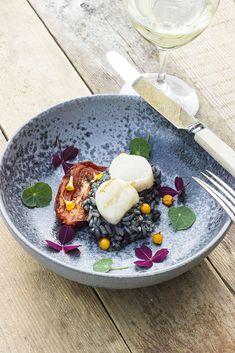 Kammusling ovenpå sort risotto kan lyde mærkværdig, og så alligevel ikke når det sorte i risottoen er blæksprutteblæk. Blækket giver både smag til risene og kontrast til de hvide kammuslinger. Udov…