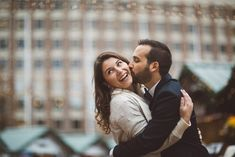A French courthouse wedding with the bride and groom holding on to one another. The groom kisses the bride on her cheek as she laughs with delight at City Hall Plaza in Boston, Massachusetts | Wedding Photography