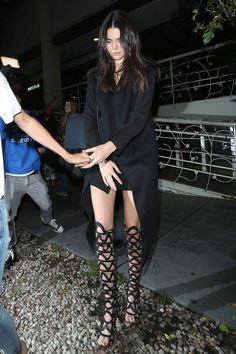 For dinner in West Hollywood, Jenner tops off an all-black look with thigh-high, Sophia Webster leather sandals