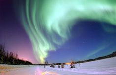 The digitally enhanced photograph taken in January 2005 shows a spectacular aurora borealis above the frozen landscape of Bear Lake, Alaska. The image was voted Wikipedia Commons Picture of the Year for 2006. Image via Joshua Strang, USAF, Wikipedia, caption via NASA