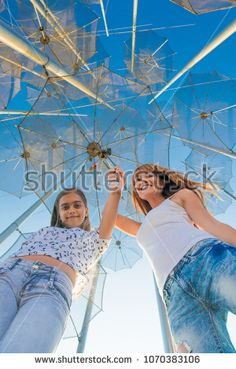 two girls under an umbrella. Young and beautiful mother and daughter under a summer umbrella. Have fun in Greece. Traveling in summer