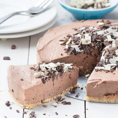A slice of no-bake chocolate cheesecake next to the remaining cheesecake covered with dark and white chocolate curls.