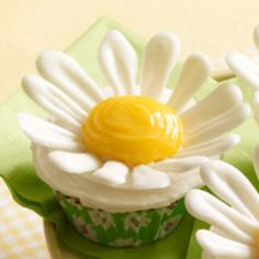 These adorable cupcakes will bring a smile to anyone's face. You could use fancy chocolate melting wafers for the flowers but this short-cut recipe uses white chocolate chips with vegetable shortening to make the petals. Once you've mastered the basic daisy cupcakes, you can experiment with other candies and treats to make all different types of flowers.