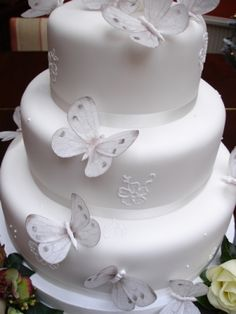 Simple and clean. White, with ribbon around the base, and butterflies. All you need to do is go to any craft store and get the decorative butterflies you want, white, or in any color. Same with the ribbon. A gorgeous do-it-yourself cake!