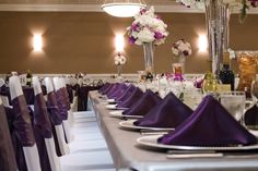 Head Table Details from a Wedding Reception held in our Grand Ballroom with seating for 280 guests. Featuring ceiling draping and a crystal chandelier! Accenting the room with fresh floral arrangements and and color palette of plum, silver & white!