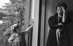 不思議そうにモデルを見る少女と、困惑するモデル嬢。1956年