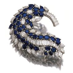 SAPPHIRE AND DIAMOND BROOCH. Of stylised scroll design, set with oval and marquise-shaped sapphires, baguette, oval, pear- and marquise-shaped diamonds, mounted in white gold.
