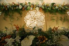 A backlit Celtic Cross backdrop surrounded with fresh flowers