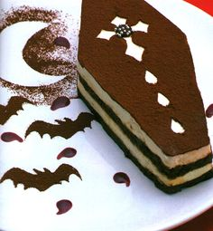 Coffin-shaped tiramisu with cocoa powder bat and moon plate art.