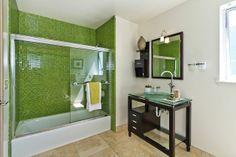 The guest suite bathroom has a glass vanity and mosaic-tiled shower and bathtub. Photo: Olga Soboleva / SF
