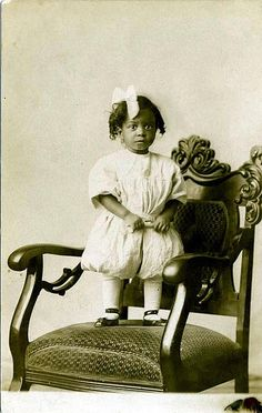 Small girl in big chair, 1910