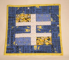 Bello. Minion Words Mug Rugs. This set of 2 Quilted Mug Rugs has Minion words on a blue background and the binding is yellow Minions. The blue border has Minions, bananas and Minion words. The center also has packed Minions, Minion eyes on blue and white Gru fabric. Blumock! The mug rugs are quilted to a yellow backing and the batting is 60% cotton and 40% polyester. The binding is hand stitched to the back for a smooth finish. The mug rugs are machine washable and can be tumbled dry or…