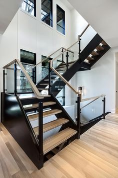 The staircase is a combination of custom iron post in a matte black finish, 10 mm glass panels, & a sawn square Oak handrail. It goes perfectly with the black stringers and natural finish hardwood treads. Black And White Stairs, Black Staircase, Staircase Railings, Modern Staircase, Staircase Design, Staircases, Custom Home Builders, Custom Homes, Calgary