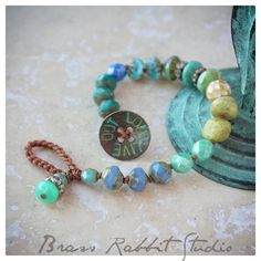 "A lovely ombre Stacker with semi precious stones, Czech glass and Swarovski crystals, knotted on waxed cotton cord with a Stacker rhinestone charm and rustic handmade artisan button that reads ""live out loud"". This bracelet fits a 6.5""-7"" wrist, can be adjusted if needed, leave me a note at checkout. · pictured layered with 2 other bracelets from my shop, available separate. · button handmade by me."