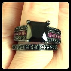 Size 7 3.80 ct black and pink CZ ring set Material Rhodium plated, black and pink CZ, size 7 AAA quality 2.20ct black princes cut, black CZ is set atop. Surrounding the solitaire are 1.0 of pink and black CZ on the engagement ring and .60 on the matching band 14k black Rhodium plated. Multiple coats have been placed over the brass base alloy for a black finish. They have a 9mm width at their largest point together. Jewelry Rings