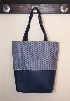 Ce sac cabas sera parfait pour vous accompagner partout ! Il pourra vous servir comme sac de shopping, sac à main, sac de cours, où pour le boulot !  Lextérieur du sac est en coton enduit japonais à motif traditionnel vagues Seigaiha blanc et bleu marine. Lavantage du coton enduit est quil est imperméable et anti-tâche. Il suffit dun coup déponge pour le nettoyer ! Le bas du sac est en simili cuir bleu marine. Les deux tissus sont séparés par un passepoil blanc.  Lintérieur du sac est en…