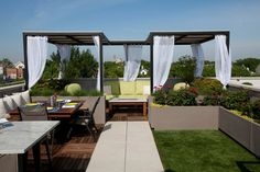 THE CITY VIEW - This backyard is short on space, but the designer utilized every square foot by adding retaining walls, patio sets for outdoor eating, and gazebos that cover the social area.  Photo by Tyrone Mitchell Photography