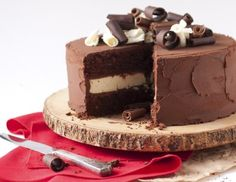 Death By Chocolate Cheesecake Cake - white chocolate cheesecake sandwiched between dark chocolate cake riddled with milk chocolate chips, en-robed in whipped dark chocolate gauche and topped with a trinity of chocolate curls.