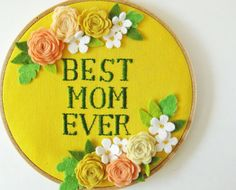 This hand-embroidered wall art with the words Best Mom Ever and felt flowers on yellow linen comes in a 6 (15cm) wooden hoop.  The words are embroidered in