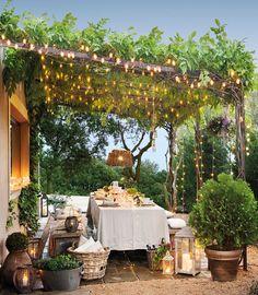 comedor bajo un porche de madera y trepadoras con luces_75