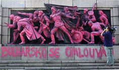 A cameraman films the figures of Soviet soldiers at the base of the Soviet Army monument in Sofia, painted in pink by an unknown artist August 21, 2013. REUTERS-Stoyan Nenov