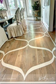 The homeowner has three young children and wanted the look of a rug without a rug.  Floors were first stained then Segreto painted the design with Sherwin Williams acrylic floor paint, which was then coated with two layers of polyurethane.