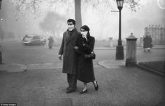 November 1953: Almost a year after the Great Smog a couple are seen wearing smog masks while walking in London for fear of contracting airborne infections.