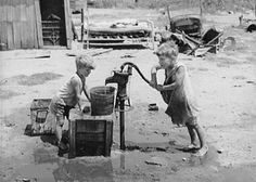 Children of Mays Avenue camp pumping water from thirty-foot well which supplies about a dozen families, Oklahoma City, Oklahoma – Notice the flour sacks they are wearing. 1939