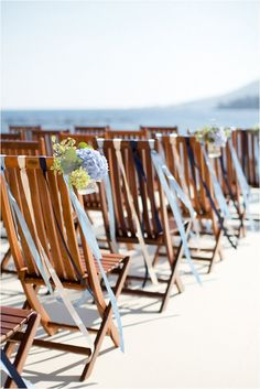 beach themed wedding - pretty light blue ribbons on chair backs catch the sea breeze at a beachside ceremony