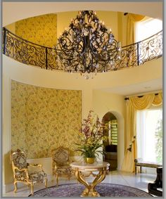 by Tracy Murdock Allied ASID  Scalamandre upholstered walls, ironwork and chandelier make for a dramatic entry