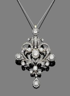A diamond brooch/pendant, circa 1890 The openwork cartouche of scrolling floral design, set throughout with old brilliant, single and rose-cut diamonds, mounted in silver and gold, to a trace-link chain, old brilliant and single-cut diamonds approx. 2.00cts total, pendant length 6.2cm