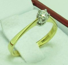 A very pretty diamond solitaire with a round brilliant cut sparkling diamond set in a white gold 6 claw setting. This ring has a plain 18ct yellow gold band. Th