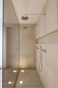 Modern Shower with long sleek shelf dual shower heads, in ground uplights and floor the ceiling glass wall.