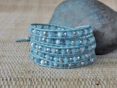 Brazilian aquamarine gemstones are mixed with white opal, light sapphire, and silver Czech fire polished beads in this softly elegant wrap bracelet. Woven onto metallic light blue leather cord with matching thread, the bracelet is finished with a silver oval metal button. Approx. 1-5/8 inches wide. Wraps around your wrist 5 times. Closure adjusts for finished lengths of 32-1/2, 33-1/2 and 34-1/2 inches to assure a good fit for most womens wrists.  ADD A CHARM: Please see the Charms Section…