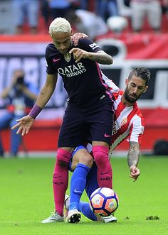 Barcelona's Brazilian forward Neymar da Silva Santos Junior (L) vies with Sporting Gijon's defender Lillo Castellano during the Spanish league football match Real Sporting de Gijon vs FC Barcelona at El Molinon stadium in Gijon on September 24, 2016. / AFP / ANDER GILLENEA
