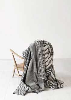 Woven throws on a vintage Ercol chair. Photographed by Yeshen Venema. Ercol Chair, Geometric Fabric, Weaving Textiles, Jacquard Weave, Design Show, Merino Wool, Monochrome, Design Inspiration, Blanket