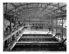 Interior of Sutro Baths. Pools with slides, four bathers beside one of the pools, date unknown.