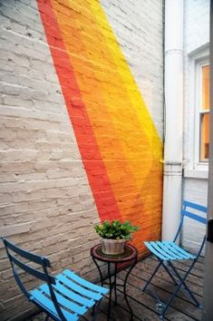 This brick wall mural certainly brightens up an outdoor space that could otherwise be an eyesore. Nice use of color to pop against the dull white wall. Pintura Exterior, Outdoor Walls, Outdoor Spaces, Outdoor Wall Paint, Outdoor Painting, Outdoor Ideas, Outdoor Chairs, Outdoor Living, Exterior Paint