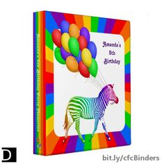 This wild 3-ring binder features a rainbow striped zebra trotting with a bunch of colorful balloons inside of a ring of primary colors. The spine and back are also colored with red, orange, yellow, green, blue, and purple. The text on the front and along the spine is fully customizable. #StudioDalio #zebraart #zebras #rainbowart #primarycolors #balloonart #birthdayaccessories #ForKids #binder #3ringbinderhardcover #keepsakes