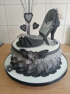 Ruffle shoe cake features a graduated Grey ruffled side design with a hand made sugar shoe and heart spray on top. The shoe is completely edible apart from the diamonte brooch and buckle!
