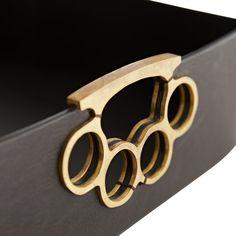 Brace yourself—the Joey Tray packs a punch. A Frank Ponterio favorite, the brass knuckle handles add an unexpected twist onthe classic espresso brown tray, finished in a warm antique brass that pops against the sleek leather. Knuckles Hand, Brass Knuckles, Bar Tray, Trays, Tray Decor, Antique Brass, Espresso, Warm, Punch
