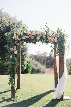 A simple four-post chuppah comes to life when wrapped in greenery and pastel colored flowers. Photo by Carmen Santorelli; Floral by Oak And The Owl