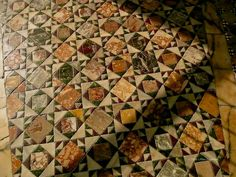 Cosmati pavement from Basilica San Marco in Venice, Italy. Bits of red and green porphyry and mottled marble cut into infinite variety on the square, glow in the evening light.