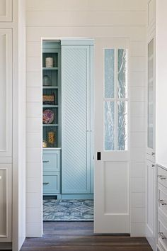 A glass paneled pocket door opens to a kitchen pantry boasting a blue vintage rug placed in front of turquoise blue cabinets.