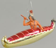"""Glass ornament of a canoe with composition Indian,  hand painted and very well detailed. 5 1/2"""" l. Paddle in left hand broken off & missing, (VG  Cond.)"""