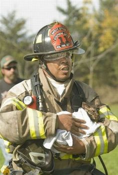 Fireman and the cat he wrapped up in a blanket. Precious..