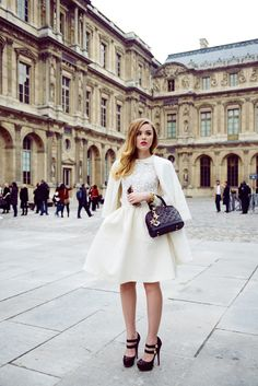 Style bloggerKristina Bazan in Paris for fashion week wearing a Zara coat, unknown vintage shirt, H skirt, and shoes, bag, and bracelet from Louis Vuitton.